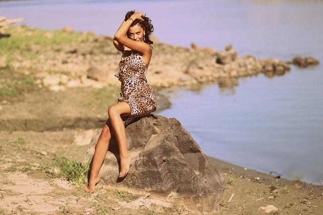 ヒョウ柄のドレス姿で岩に座る外国人女性