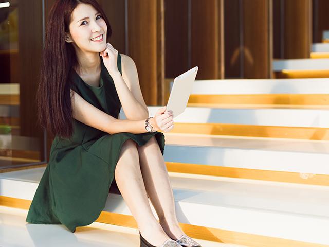 緑のワンピースを着て階段に座っている女性