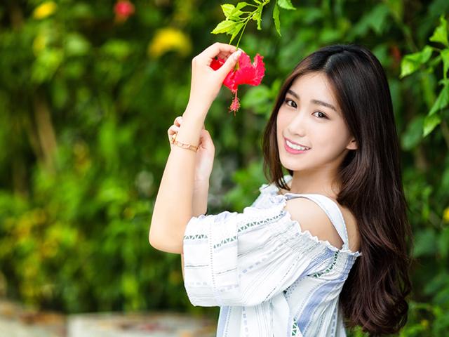 赤い花を持っている女性