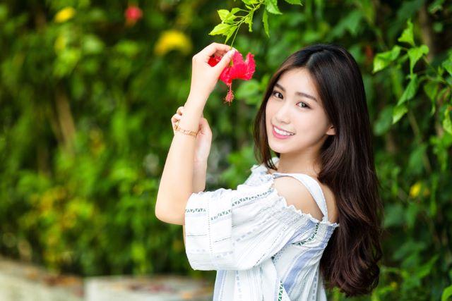 ハイビスカスの花を手に持つ女性