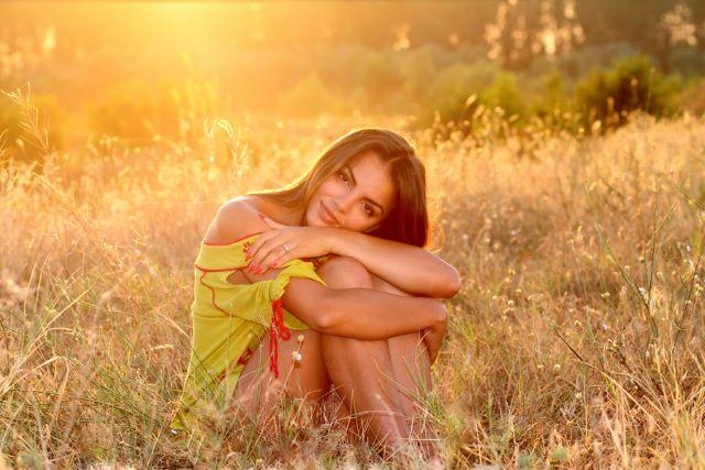 夕暮れの草むらで膝を抱える外国人女性