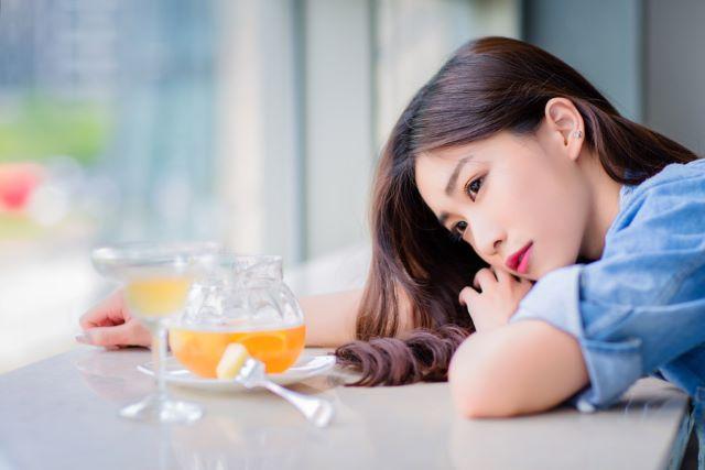 カフェのテーブルに突っ伏す女性