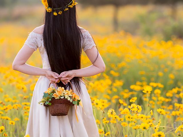 黄色いお花を摘んでいる女性