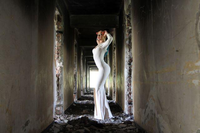 ドレス姿で廃墟の建物の中に立つ外国人女性