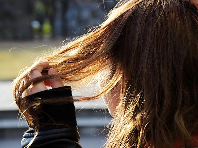 自分の髪の毛に触っている女性
