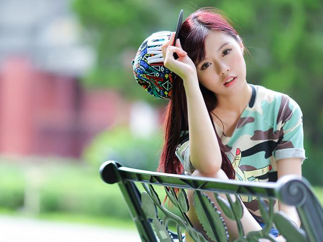 迷彩柄の服を着てベンチに座っている女性