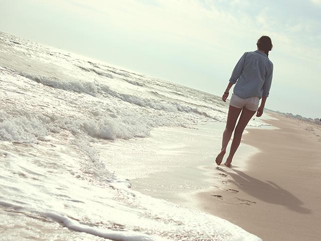 海を1人で歩いている女性