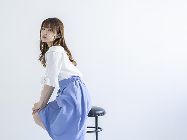 丸椅子に座っている青いスカートの女性