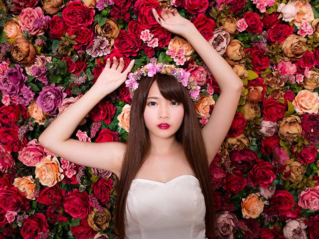 花に囲まれて両手を上げている女性