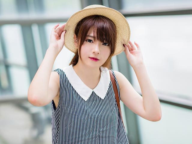 麦わら帽子をかぶっている大学生風の女性