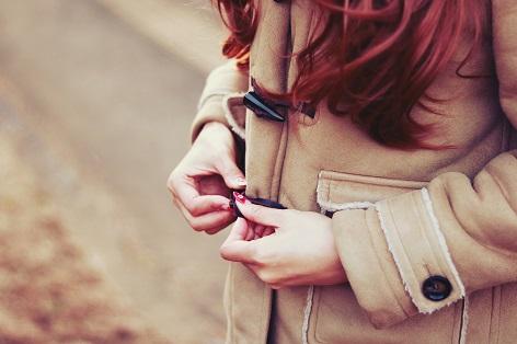 コートのボタンをいじる女の子