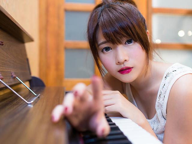ピアノにもたれかかっている女性