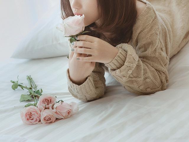花を持ってうつ伏せになっている女性