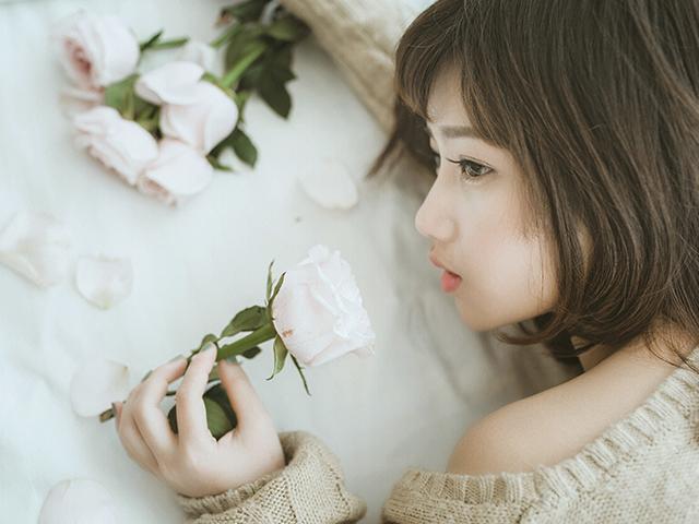 花を持って寝転んでいる女性