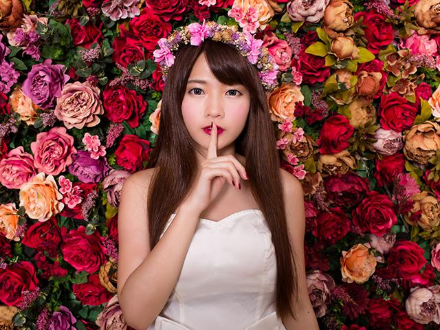 花に囲まれて人差し指を立てている女性