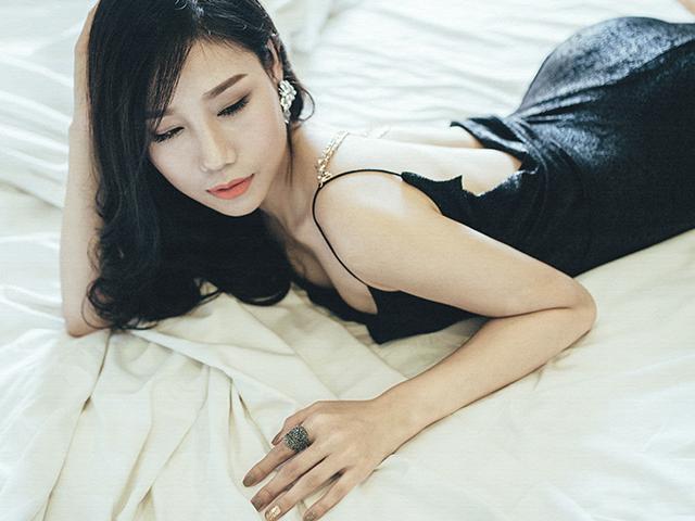 黒いドレスで寝転んでいる妖艶な女性