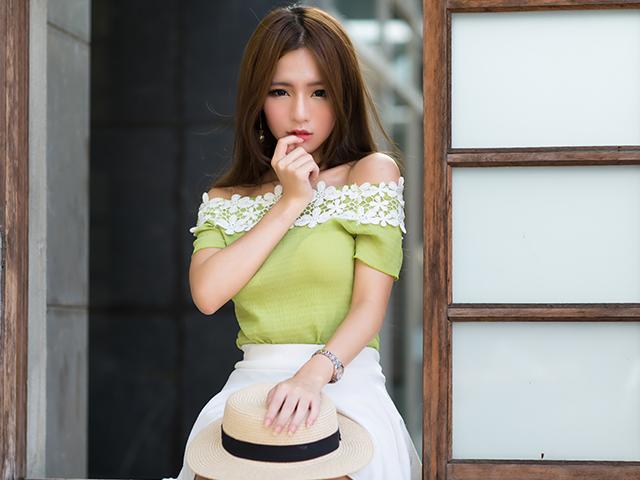黄緑色の服を着て指を咥えている女性