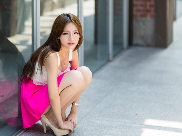 ピンクのスカートを履いてしゃがみこんでいる女性