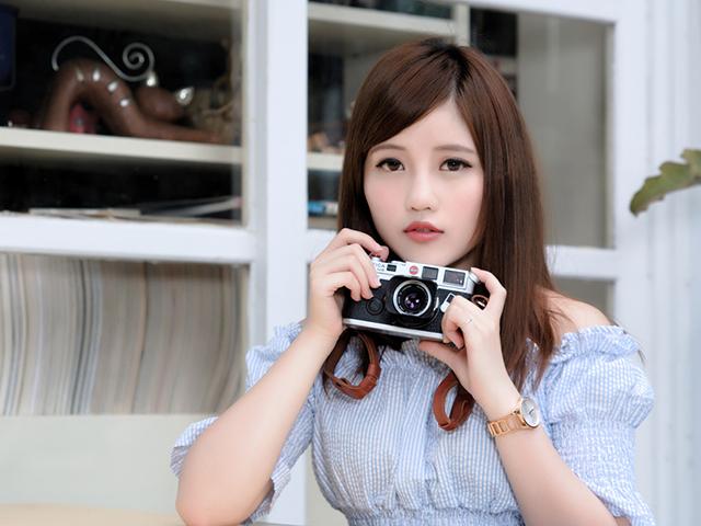 カメラを持っている真顔の女性