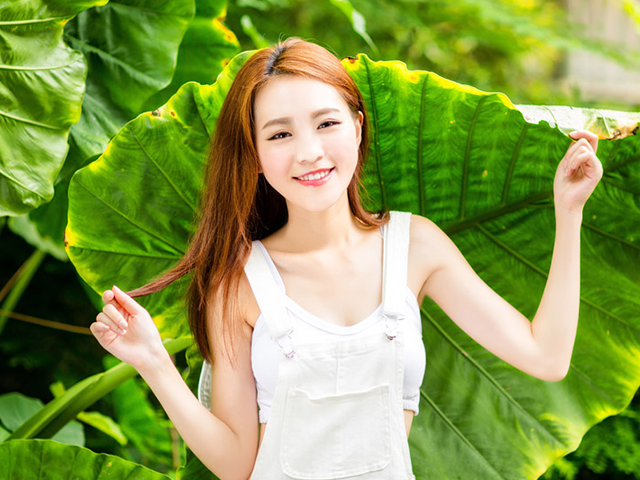 葉っぱを背景にしている女性