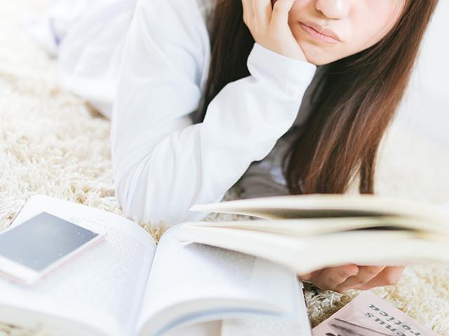 スマホと参考書で調べながら勉強している女性