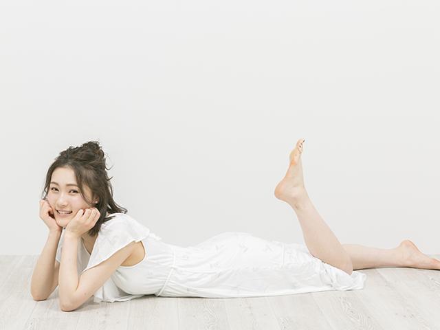 白いワンピースで寝そべる女性