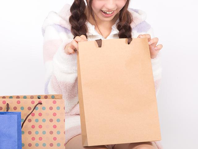 買い物袋の中身を確認して喜んでいる女性