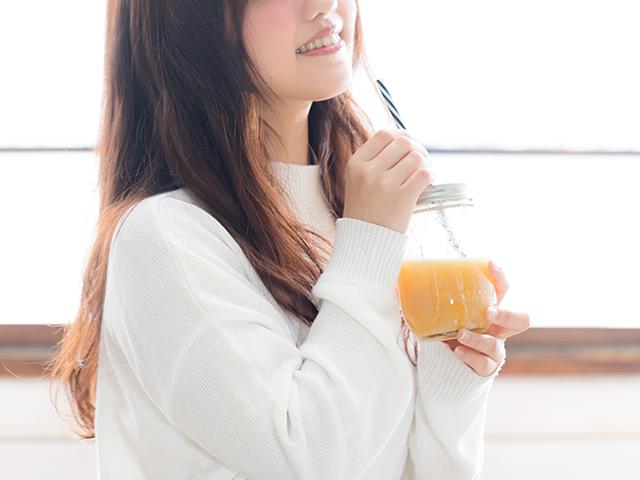 オレンジジュースを飲んでいる女性