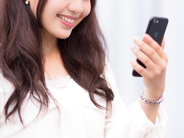 スマホでサイトを見て微笑んでいる女性