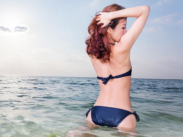 海で膝立ちする女性