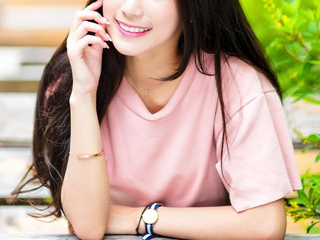 こちらに向かって微笑みかけているピンクシャツの女性