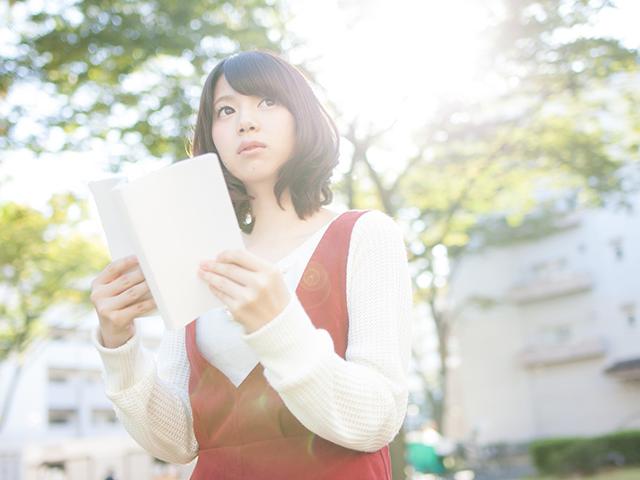 屋外で読書をしている女性