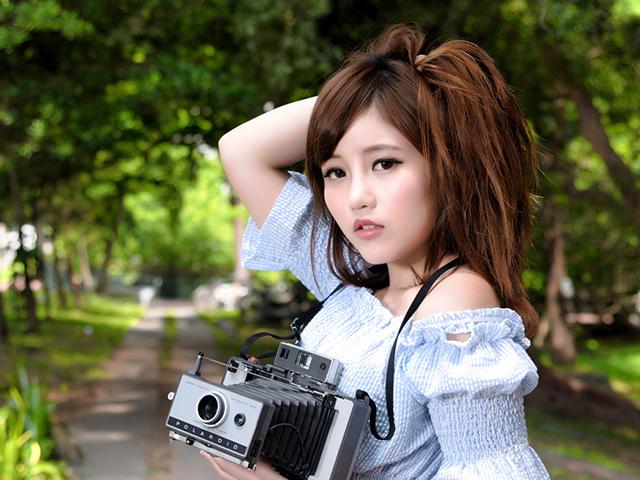 古いカメラを持って髪を乱している女性
