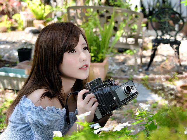 草の写真を撮ろうとしている女性