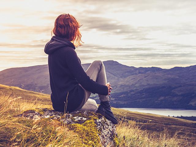 遠くの山を見ている女性