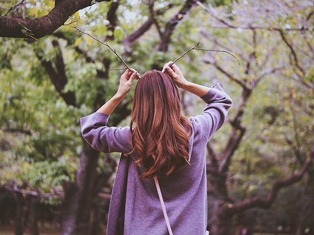 木の枝で遊んでいる女性