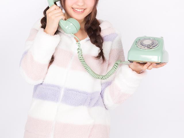 パジャマ姿で電話をしている女性