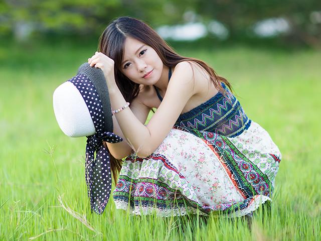 芝生にしゃがみこんでいる女性