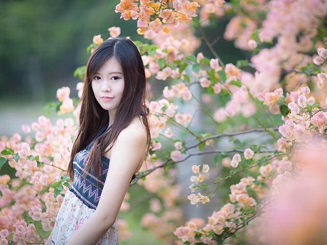 花の前に立っている女性