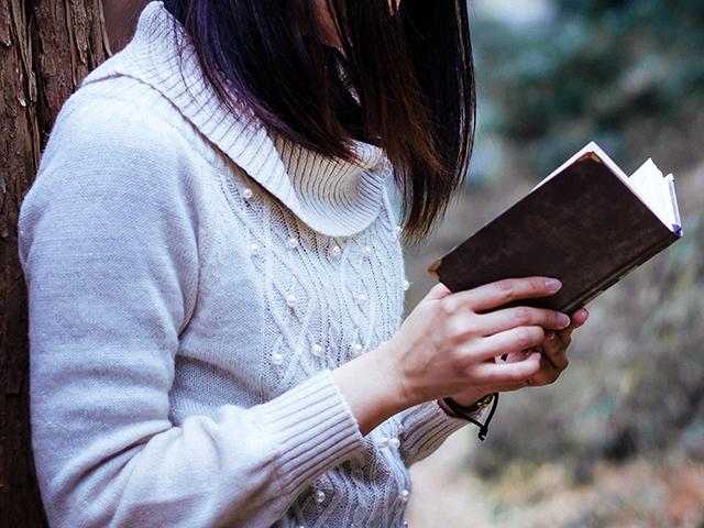 木にもたれかかって読書する女の子