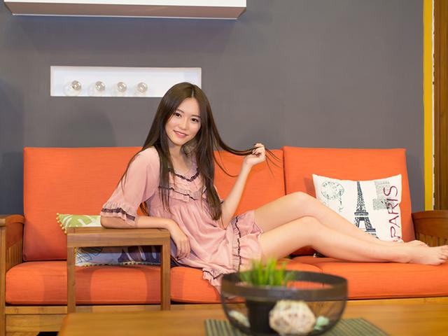 オレンジのソファに座っている女性