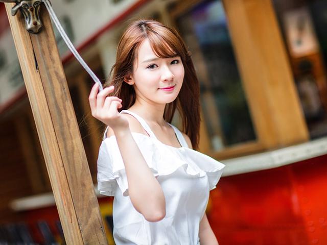 白いオフショルを着て木の柱に寄り添う女の子