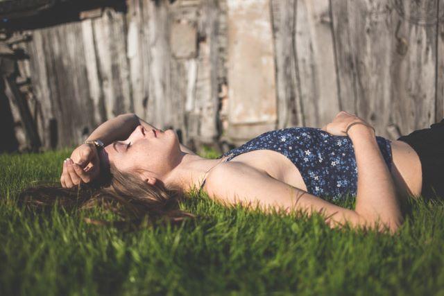 芝生の上で寝ている外国人女性