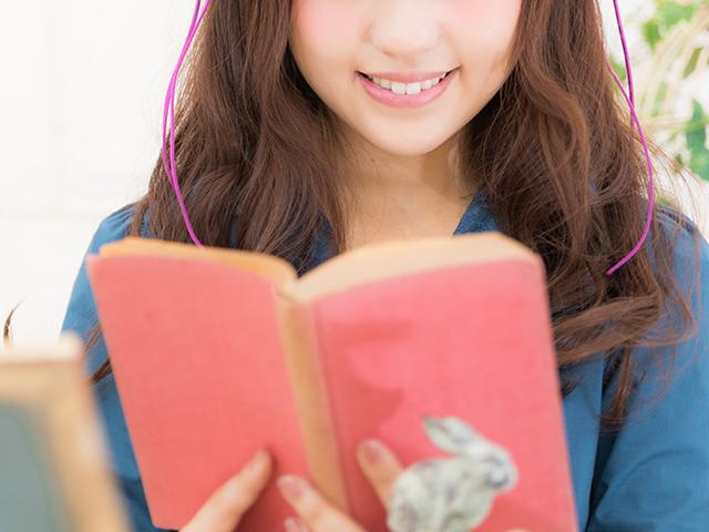 赤い表紙の本を読んでいる女性