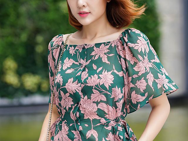 緑地にピンクの花柄のワンピースを着た女性