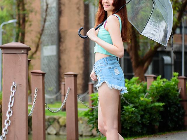 小雨で傘を指しているスタイルバツグンの女性