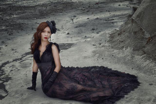 黒のドレス姿で地面に横座りする女性
