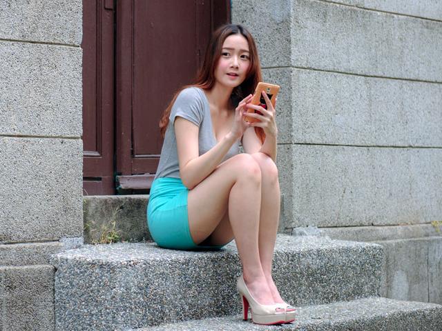 ドアの外で座りながら携帯をいじる女性