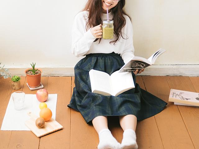 ジュース飲みながら本を読んでいる女性