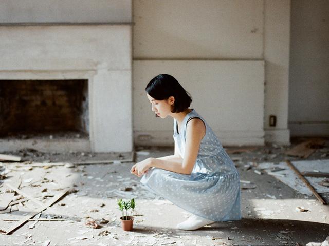 小さな植木鉢をみつめる清楚な女性